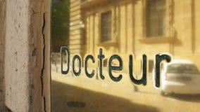Doktorska szyldowa plakieta robić od złota z odbiciem pedestrians i miasto zbiory wideo