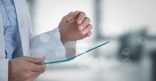 Doktorska w połowie sekcja z szklanym przyrządem za bokeh przeciw rozmytemu popielatemu biuru obrazy royalty free