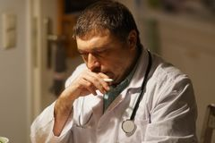 Doktorska writing recepta przy jego biurkiem zdjęcie stock