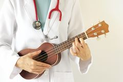 Doktorski bawić się ukulele, Muzycznej terapii pojęcie Zdjęcie Stock