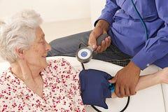 Doktorski bierze ciśnienie krwi starszy pacjent w domu Zdjęcie Stock