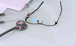 Doktorski biurko z szkłami, klawiaturą, mysz ochraniaczem i stetoskopem z, zdjęcia stock