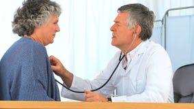 Doktorski brać bicie serca jego dojrzały pacjent zdjęcie wideo