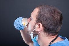 Doktorski być ubranym szoruje popijanie od filiżanki z pigułkami Obraz Royalty Free