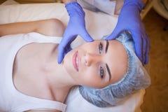 Doktorski cosmetologist robi twarzowemu masaż dziewczyny zdrojowi fotografia royalty free