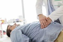Doktorski częstowanie żołądek pacjent w egzaminacyjnym pokoju zdjęcie stock