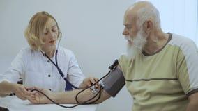 Doktorski czeka puls starszy mężczyzna z mechanika stetoskopem i tonometer zdjęcie wideo