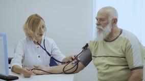 Doktorski czeka puls stary człowiek z tonometer i stetoskopem zbiory wideo