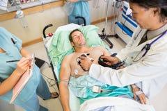 Doktorski Defibrillating Męski pacjent W szpitalu zdjęcia stock