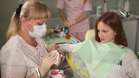 Doktorski dentysta uczy nastolatka szczotkować jego zęby na przykładzie atrapa zbiory wideo