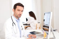 Doktorski działanie przy biurem z pielęgniarką w tle fotografia stock
