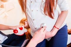 Doktorski egzamininujący kobieta w ciąży w świetle odziewa fotografia royalty free