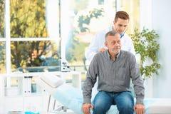 Doktorski egzamininuje dojrzały pacjent z stetoskopem w szpitalu obrazy stock