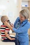 Doktorski egzamininuje dzieciaka ` s ucho Fotografia Stock