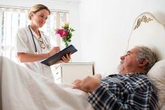 Doktorski egzamininuje męski pacjent w karmiącym domu Obrazy Stock