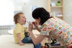 Doktorski egzamininuje małego dziecka ` s gardło Obrazy Stock