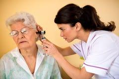 Doktorski egzamininuje ucho starsza kobieta zdjęcia royalty free
