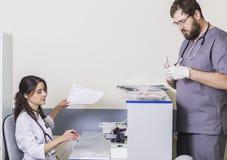 Doktorski kobiety obsiadanie przy stołem, męska lekarka jest przy szpitalem z dokumentami Fotografia Royalty Free