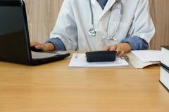 doktorski lekarz z stetoskopem kalkuluje medycznych opłata koszty, dochód & lekarz praktykujący używa kalkulatora przy szpitalem obrazy stock