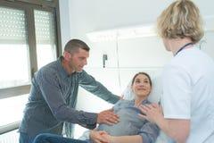 Doktorski mąż i ciężarna żona przy szpitalem Zdjęcia Royalty Free