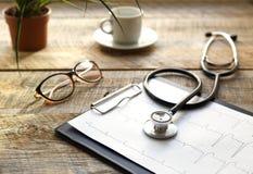 Doktorski miejsce pracy z stetoskopem przy drewnianym stołem Zdjęcia Royalty Free
