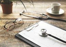 Doktorski miejsce pracy z stetoskopem przy drewnianym stołem Obrazy Royalty Free