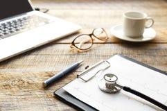 Doktorski miejsce pracy z stetoskopem przy drewnianym stołem Obraz Stock