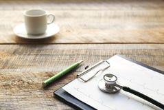 Doktorski miejsce pracy z stetoskopem przy drewnianym stołem Zdjęcie Royalty Free