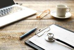 Doktorski miejsce pracy z stetoskopem przy drewnianym stołem Zdjęcie Stock