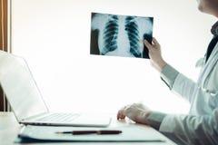 Doktorski mienia promieniowania rentgenowskiego film przy podołkiem w szpitalnym biurze obraz royalty free