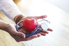 Doktorski mienie stetoskop i czerwieni serce na rękach z białym zdrojem zdjęcia royalty free