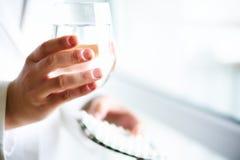 Doktorski mienie szkło woda z lekiem, pigułki, biały tło kosmos kopii pojęcie kłama medycyny pieniądze ustalonego stetoskop Zdjęcie Stock