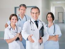 Doktorski ofiara uścisk dłoni podczas gdy stojący z drużyną w szpitalu Obraz Stock