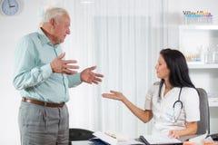 Doktorski opowiadać jej męski starszy pacjent przy biurem Obrazy Stock