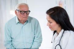 Doktorski opowiadać jej męski starszy pacjent przy biurem zdjęcie royalty free