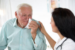 Doktorski opowiadać jej męski starszy pacjent przy biurem Fotografia Stock