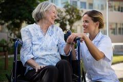 Doktorski opowiadać kobiety obsiadanie na wózku inwalidzkim w parku zdjęcia royalty free