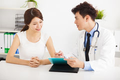 Doktorski opowiadać z żeńskim pacjentem w biurze Obrazy Stock