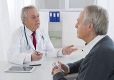 Doktorski opowiadać jego starszy pacjent przy biurem Zdjęcia Royalty Free