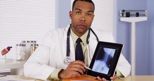 Doktorski opowiadać z promieniowaniem rentgenowskim na pastylce Fotografia Stock