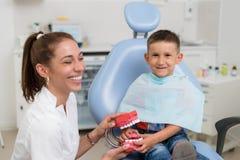 Doktorski ortodonta bawić się z chłopiec w stomatologicznym biurze zdjęcia royalty free