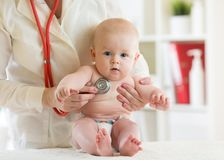 Doktorski pediatryczny egzamininuje małe dziecko w klinice Dzieci zdrowie pojęcie fotografia royalty free