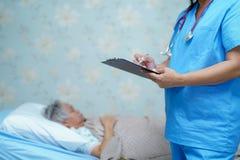 Doktorski pisze puszek diagnoza na schowku podczas gdy Azjatycki senior lub starszy starej damy kobiety lying on the beach na łóż obrazy royalty free
