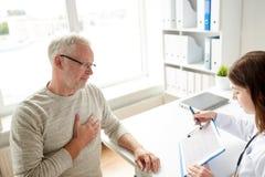 Doktorski pokazuje kardiogram stary człowiek przy szpitalem Zdjęcie Stock