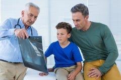 Doktorski pokazuje promieniowanie rentgenowskie raport pacjent i jego wychowywamy Zdjęcia Royalty Free