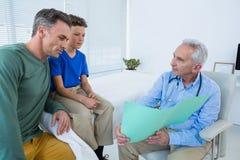 Doktorski pokazuje raport medyczny pacjent i jego wychowywamy Zdjęcie Stock