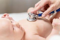Doktorski słuchający bicie serca nowonarodzony dziecko stetoskopem zdjęcie royalty free