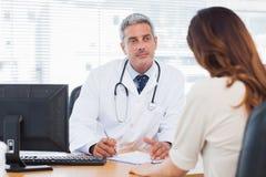 Doktorski słuchanie jego pacjent opowiada o jej chorobie zdjęcie royalty free
