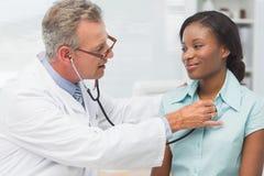 Doktorski słuchanie rozochocona młoda pacjent klatka piersiowa z stetoskopem obraz stock