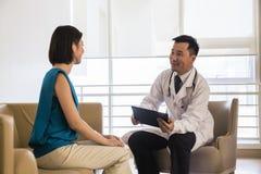 Doktorski siedzący puszek i ordynacyjny pacjent w szpitalu obrazy stock